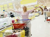 happy woman with arms in the air standing behind a full shopping cart inside a store