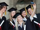 group of students in graduation gowns smiling and posing for a group selfie