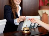 hotel receptionist handling over key to guest