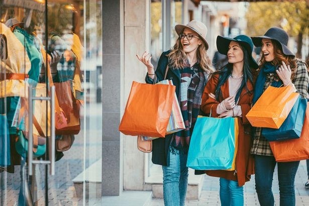 three women shopping together with shopping bags