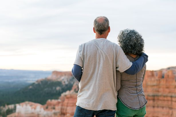 senior couple looking over canyon, view of their backs