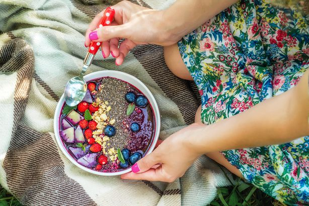 acai bowl with chia seeds and berries over blanket, held by two hands with nail polish