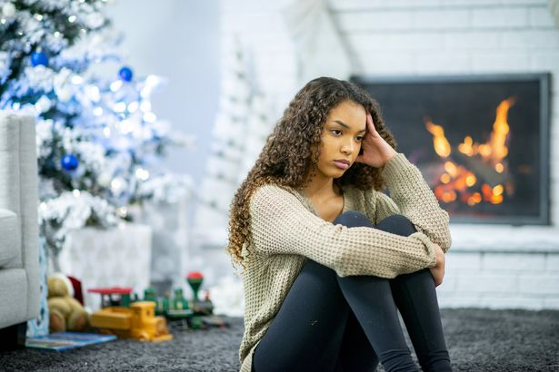 woman sitting with tense expression and hand to head with christmas tree and fireplace background
