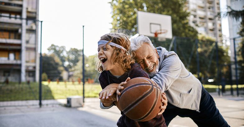 senior man hugging grandchild, playing basketball together