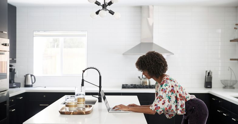 woman in kitchen downloading files on computer, standing, on her way out