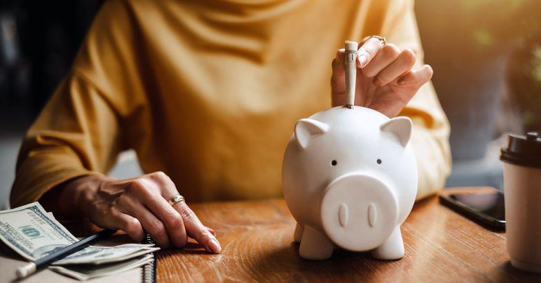 senior woman putting money in piggy bank