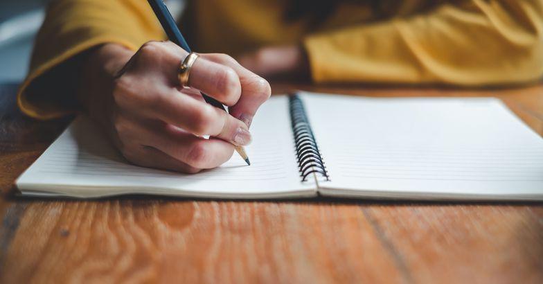 close-up of hands journaling