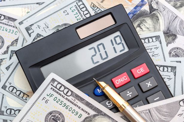 Calculator With Numbers 2019 And Pen On Background Of Dollar Bills