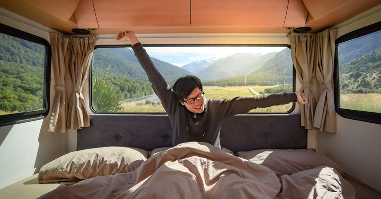 man stretching arms waking up in bed in rv, mountain valley in background