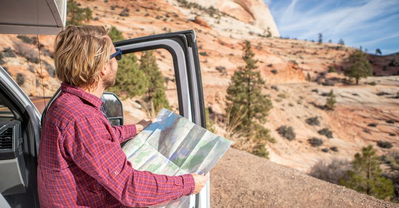 man looking at map stepping outside rv