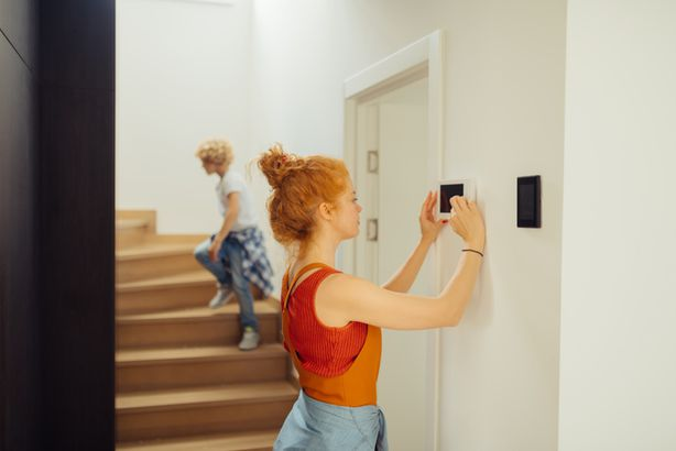 Woman using a smart thermostat