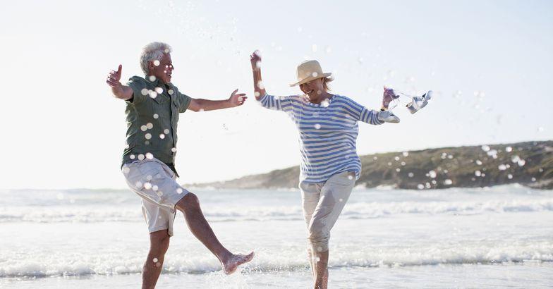 senior couple splashing in ocean