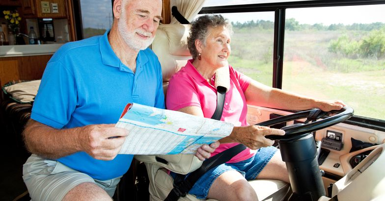 couple driving rv and looking at map