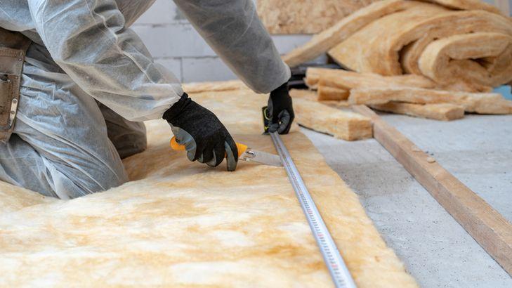 Man adding attic insulation