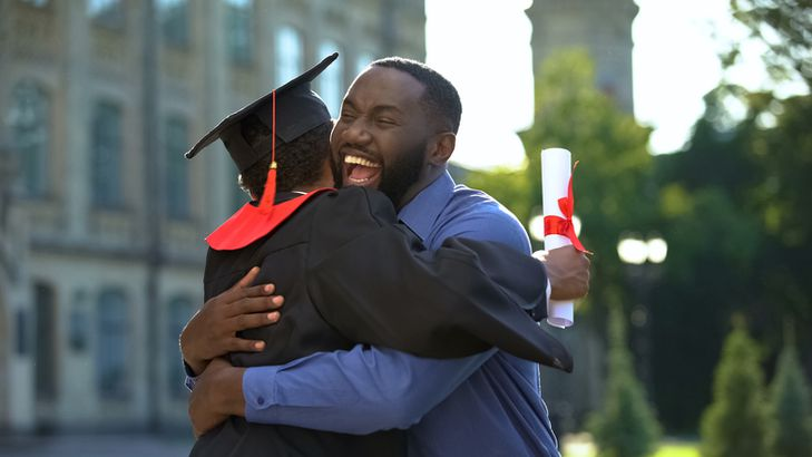 Father and son hugging after graduation