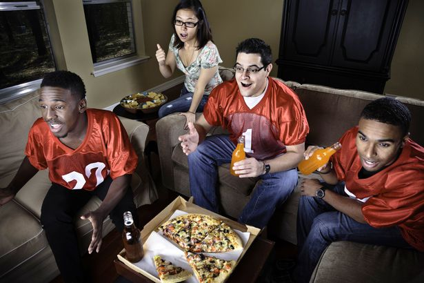group of friends in football outfits eating pizza watching super bowl