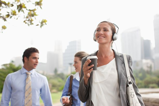 businesswoman listening to headphones and carrying coffee outside