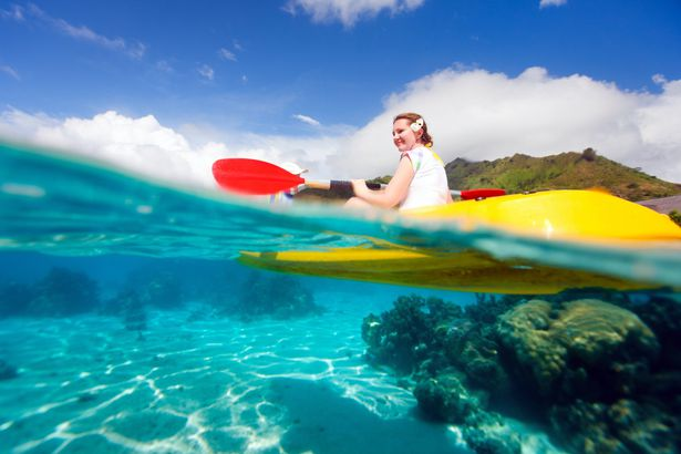 young woman kayaking over coral reef