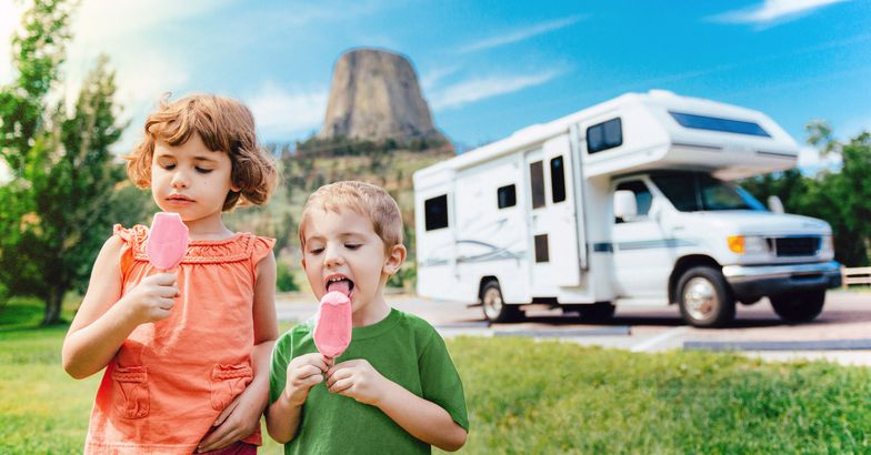 two children walking in grass eating ice cream, rv in distance
