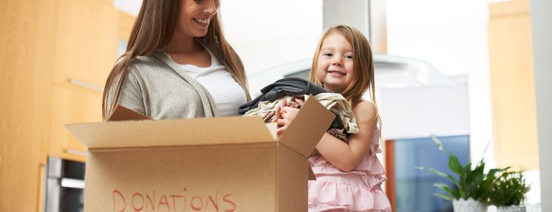 daughter helping mother with donation box at home