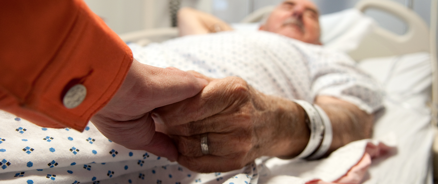 man lying in a hospital bed holding wife's hand