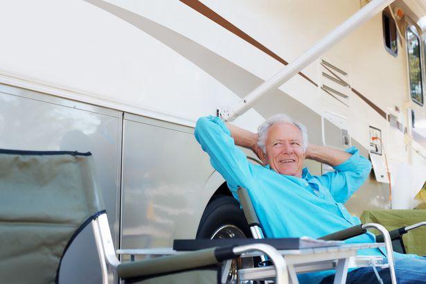 senior man leaning back smiling sitting outside rv