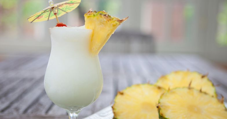 piña colada next to pineapple slices on plate on wooden table