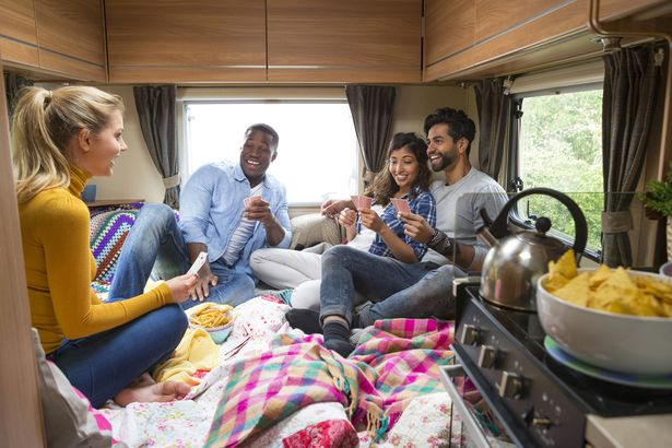 group of friends in bed in rv with stove in foreground