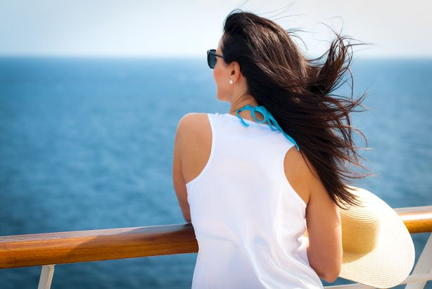 woman looking out to the ocean on a cruise deck