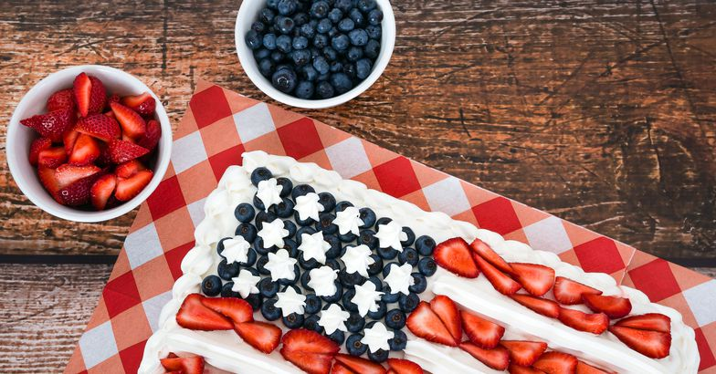 flag cake on wooden surface, blueberries and strawberries