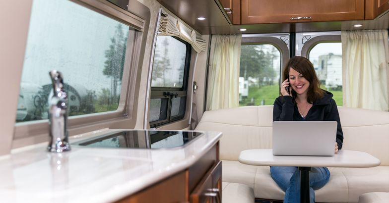 woman using laptop and speaking on phone smiling in rv, rain outside