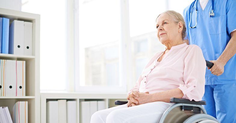 nurse pushing senior woman in wheelchair down hallway