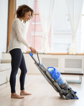 woman vacuuming living room with upright vac