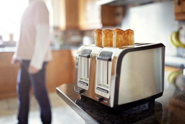 toaster on countertop of kitchen with person in background