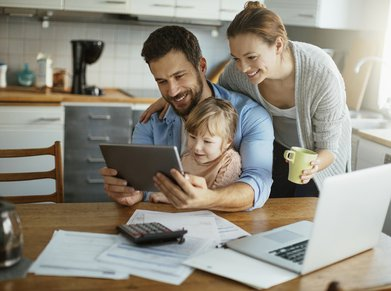 young family at kitchen table with laptop, calculator, and tablet