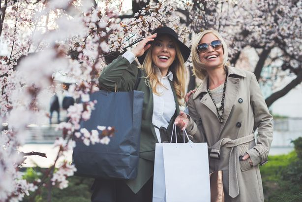 two women with shopping bags, cherry blossoms in background