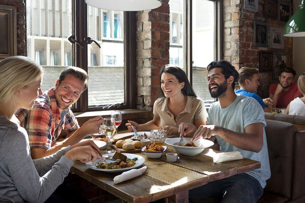 group of adults smiling eating at restaurant with brick interior, framed photos on wall, booth with other adults in background