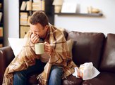 man sitting on living room couch sick with the flu