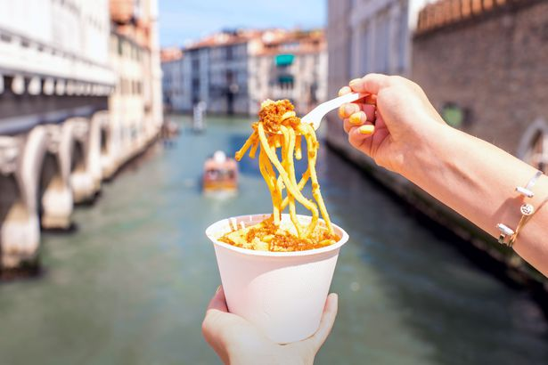hand holding cup of pasta with fork pulling it out with venice canal in background