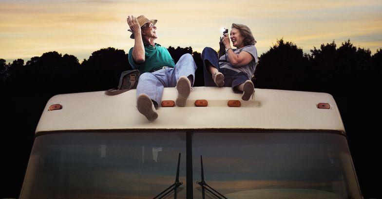 senior couple taking photos on rv roof