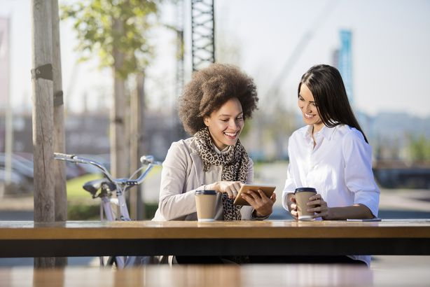 two women drinking coffee outside while sitting and looking at a tablet