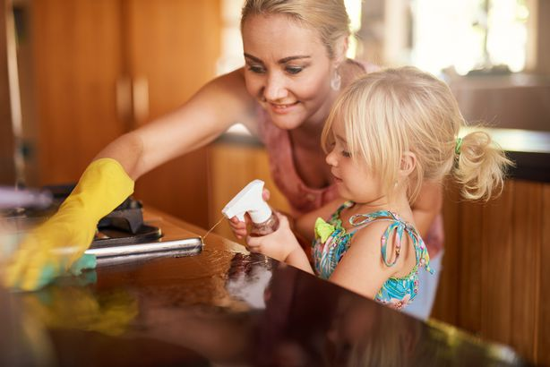 mom and little daughter cleaning kitchen together