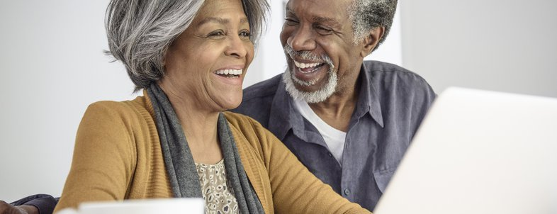 senior African American couple using laptop and laughing