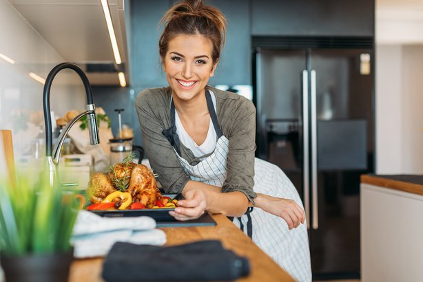 woman wearing apron with cooked turkey in kitchen