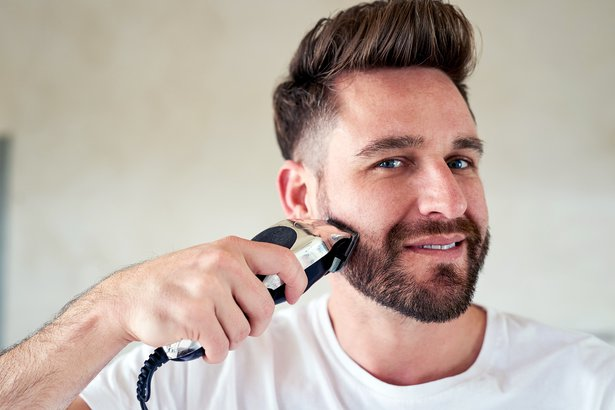 man using electric shaver on beard