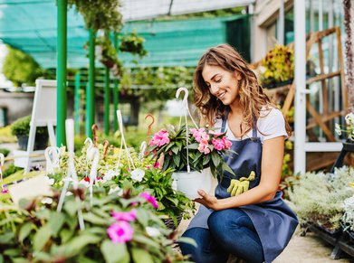 Woman Worker Looking At Flowers In Gardening Center