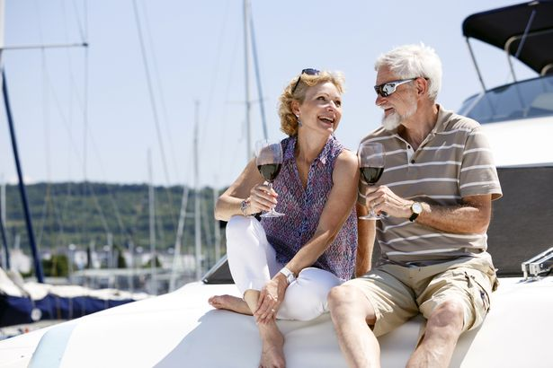 two adults enjoying wine on a boat, smiling