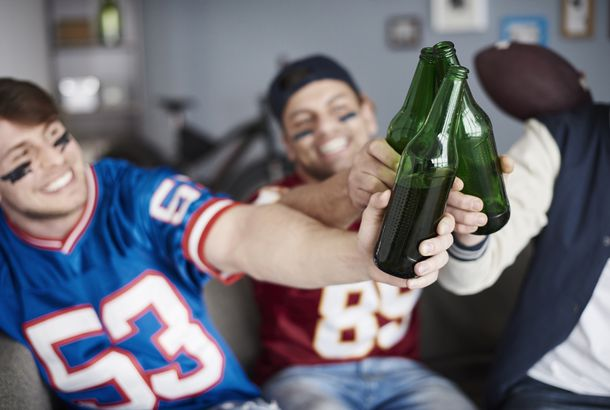 American football fans make a toast indoors