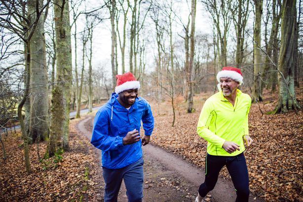 two men running with christmas hat in winter scene