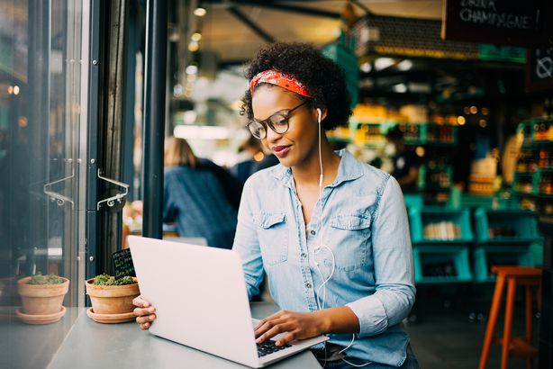 young African woman working online in a cafe